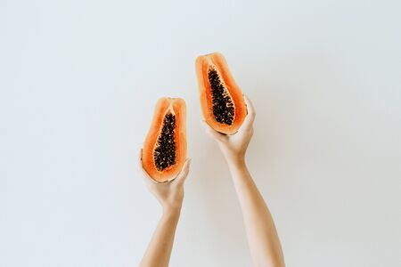 Summer and travel concept. Young woman's hands holding exotic tropical orange papaya fruit. Minimalistic seasonal vegetarian background. Front view. 免版税图像