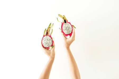 Summer and travel concept. Young woman's hands holding exotic tropical dragon fruit. Minimalistic seasonal vegetarian background. Front view.
