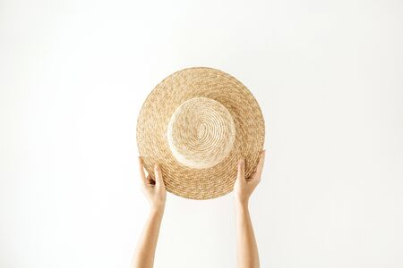 Minimalistic summer and travel concept. Womans hands holding a straw yellow hat. Front view.