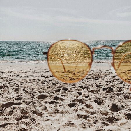 Tropical beautiful beach with white sand, foot steps, blue sea and yellow sunny sunglasses.  Summer travel or vacation concept. Minimalistic background. Stock Photo