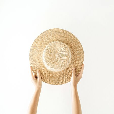Minimalistic summer and travel concept. Woman's hands holding a straw yellow hat. Front view. Archivio Fotografico