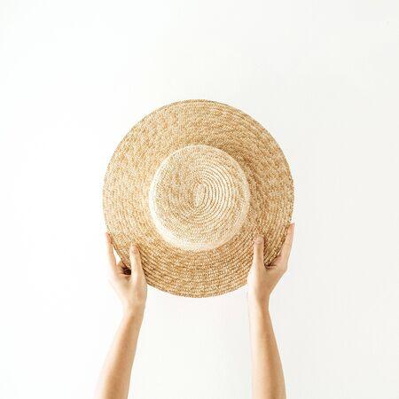 Minimalistisches Sommer- und Reisekonzept. Die Hände der Frau, die einen strohgelben Hut halten. Vorderansicht. Standard-Bild