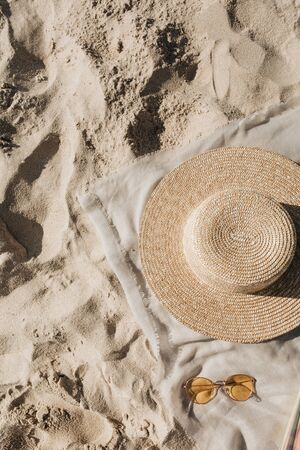 Tropical beautiful beach with white sand, foot steps, neutral blanket with straw hat, sunglasses. Relaxing atmosphere. Summer travel or vacation concept. Minimalistic background.