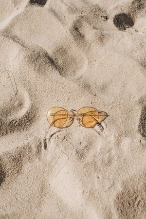 Tropical beautiful beach with white sand, foot steps and yellow sunny sunglasses.  Summer travel or vacation concept. Minimalistic background.