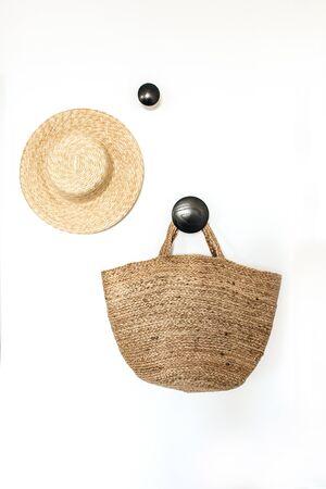 Straw hat and bag on blank hanger. Minimal modern Scandinavian interior design concept. Stock Photo