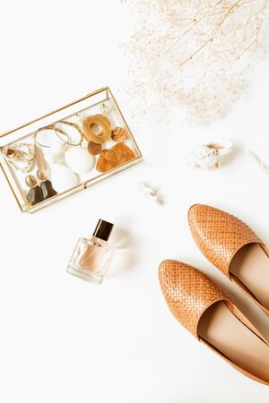 Female fashion pastel composition with trendy accessories. Perfume, shoes, earrings, flowers bouquet on white background. Flat lay, top view styled pale lifestyle concept. Imagens