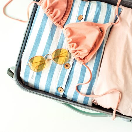 Womens summer bikini swimsuit, stylish sunglasses and dress in luggage. Flat lay, top view fashion travel lifestyle concept.