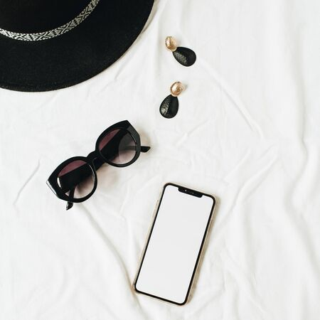 Fashion mockup composition with elegant womens accessories on white linen. Hat, sunglasses, earrings, smartphone with copy space screen. Flat lay, top view minimal lifestyle fashion blog concept.