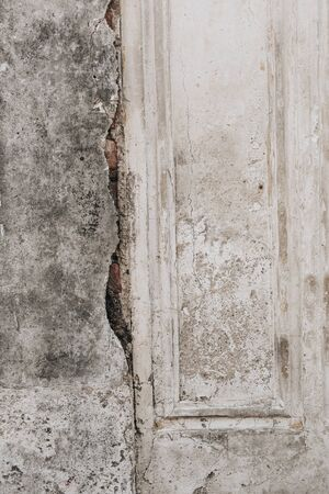 An old shabby pale beige door with gray cement wall with cracks. Vintage and retro concept. Neutral background. Stock fotó