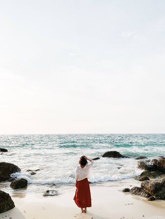 A beautiful young woman in red skirt and white shirt standing on the beach watching at blue sea with waves, rocks and cream sky. Open space for text. Summer and travel concept.