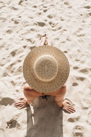 Summer vacation fashion concept. Beautiful young, tanned woman with a straw hat is lying and relaxing on tropical beach with white sand. Top view, flat lay. Standard-Bild - 129781824