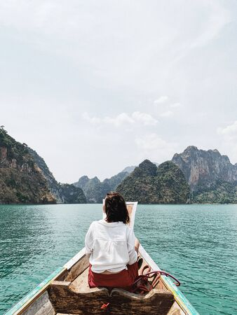 Young woman in red skirt and white blouse sitting on wooden boat watching at exotic and tropical dark green big islands with rocks and turquoise lake at Cheow Lan Lake, Khao Phang, Ban Ta Khun District, Thailand. Travel holiday and adventure concept. Standard-Bild - 129781825
