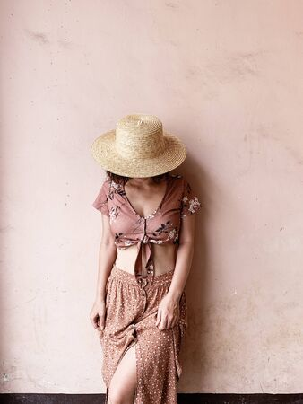Fashion female concept. Young woman in pink skirt, short pink blouse and straw hat standing near pink wall. Beauty blog. Standard-Bild - 129781828