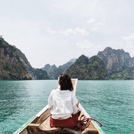 Mujer joven en falda roja y blusa blanca sentada en un barco de madera mirando exóticas y tropicales islas grandes de color verde oscuro con rocas y lago turquesa en el lago Cheow Lan, Khao Phang, distrito de Ban Ta Khun, Tailandia. Viajes concepto de vacaciones y aventuras. Foto de archivo