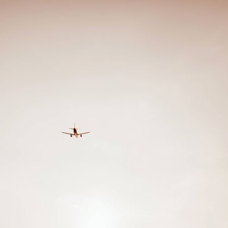Airplane flying in the sky at sunset. Travel, vacation and holiday concept. Vintage and retro tones with warm beige colors filter. Minimalistic background. Standard-Bild - 129781837