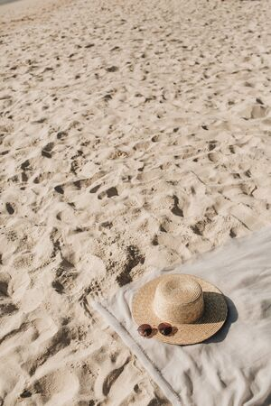 Tropical beautiful beach with white sand, foot steps, neutral blanket with straw hat and sunglasses. Relaxing atmosphere. Summer travel or vacation concept. Minimalistic background. Standard-Bild - 129781865