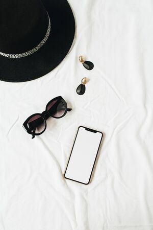 Fashion mockup composition with elegant women's accessories on white linen. Hat, sunglasses, earrings, smartphone with copy space screen. Flat lay, top view minimal lifestyle fashion blog concept. Standard-Bild - 129781944