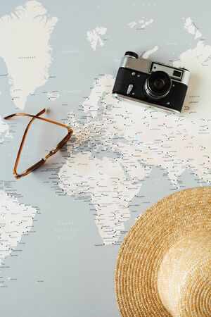 Minimal world map with pins, retro camera, sunglasses, straw hat. Flat lay vacation travel planning composition. Travel photographer concept. 스톡 콘텐츠 - 129781963