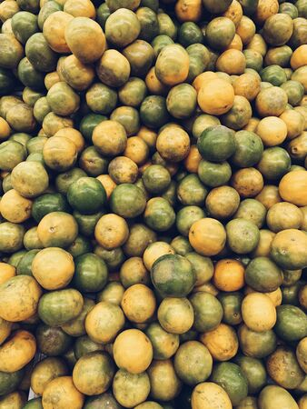 A great amount of green and yellow limes. Vegetarian, vegan, healthy and summer concept. Natural sunny juicy background, pattern and texture. Top view, flat lay. Standard-Bild - 129781976