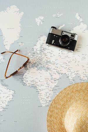 Minimal world map with pins, retro camera, sunglasses, straw hat. Flat lay vacation traveling planning composition. Traveler tourist concept. Standard-Bild - 129781983