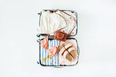 Hand luggage with bikini, sunglasses, slippers, retro camera and dress on white background. Flat lay, top view travel vacation fashion composition. Standard-Bild - 129782012