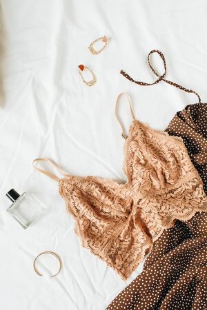 Flatlay fashionable female underwear, clothes and accessories on white linen. Ginger bra, dress, perfume, earrings, bracelet, pillow. Top view fashion lifestyle beauty collage. Stockfoto