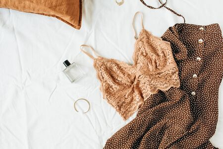 Fashion trendy underwear composition. Bra, perfume, evening dress on white linen background. Flat lay, top view beauty blog  social media minimal concept.