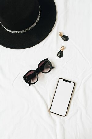 Fashion mock up background with womens accessories on white linen. Hat, sunglasses, earrings, smart phone with blank copy space screen. Flat lay, top view minimal lifestyle fashion blog template. Stockfoto