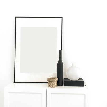 Photo frame on chest of drawers with decoration at white wall. Minimal modern Scandinavian interior design concept.