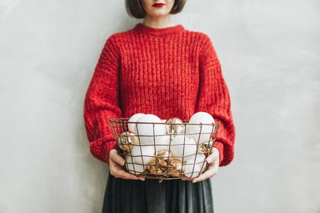 Young pretty woman with red knitted sweater and grey skirt holding in her hands big basket of christmas gold and white balls. Minimal styled christmas and new year concept.