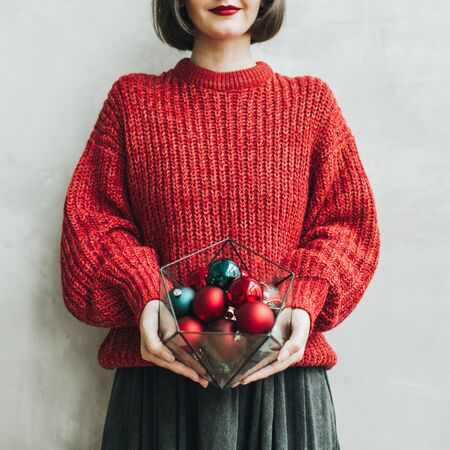 Young pretty woman with red lips, red knitted sweater and grey skirt holding in her hands geometrical vase with christmas red and blue toys. Minimal styled christmas and new year concept.