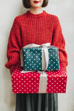 Young pretty woman with red knitted sweater and grey skirt holding in her hands big handmade gift boxes made of blue and red paper with white polka dots and grey ribbon. Minimal styled christmas and new year concept.