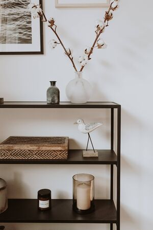 Modern scandinavian nordic living room with beautiful details such as black shelves, vases, frames, wooden caskets, cotton agains white wall. Scandi design interior concept.