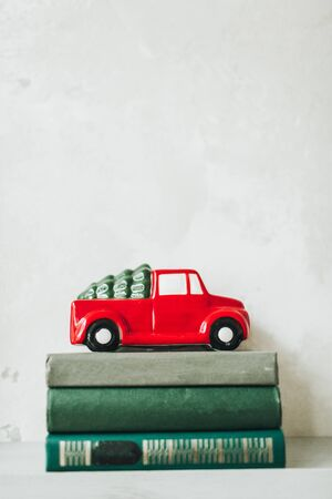 Christmas  New Year composition. Traditional toy of christmas red car with fir on the roof standing on books. Winter holidays concept.