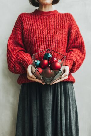 Young pretty woman with red knitted sweater and grey skirt holding in her hands geometrical vase with christmas red and blue toys. Minimal styled christmas and new year concept.