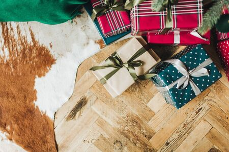 Christmas  New Year composition. Festive handmade gift boxes wrapping in red, blue and beige colors paper lying under christmas tree on wooden floor. Flat lay, top view. Winter holidays concept.