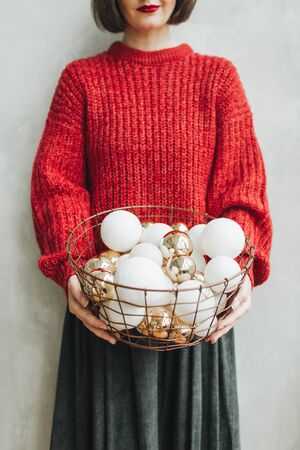 Young pretty woman with red knitted sweater and grey skirt holding in her hands big basket of christmas gold and white toys. Minimal styled christmas and new year concept. Stok Fotoğraf