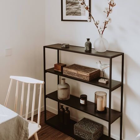 Modern scandinavian nordic living room with beautiful details such as black shelves, vases, frames, wooden caskets, cotton, wooden beige chair, white table. Scandi design interior concept.
