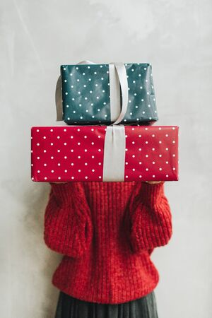 Young pretty woman with red knitted sweater and grey skirt holding in her hands big handmade gift boxes made of blue and red paper with white polka dots and grey ribbon. Minimal styled creative christmas and new year concept.
