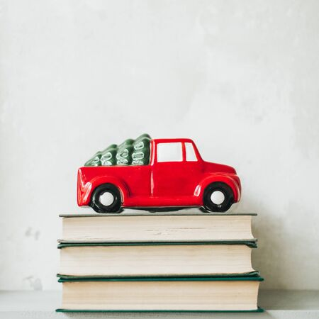 Christmas / New Year composition. Traditional toy of christmas red car with fir on the roof standing on books. Minimal winter holidays concept. Christmas card.