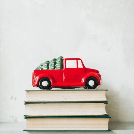 Weihnachten/Neujahr-Zusammensetzung. Traditionelles Spielzeug des roten Weihnachtsautos mit Tanne auf dem Dach, das auf Büchern steht. Minimales Winterferienkonzept. Weihnachtskarte. Standard-Bild