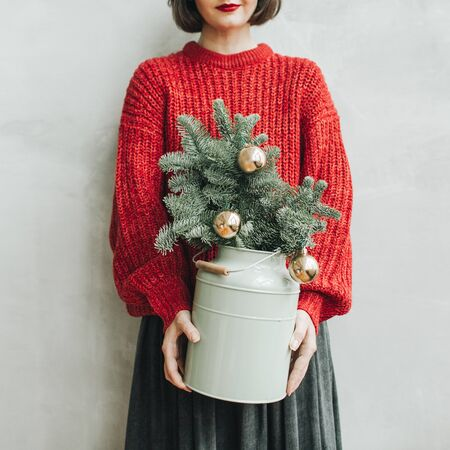 Young pretty woman with red knitted sweater and grey skirt holding in her hands vintage mint watering pot with christmas fir branches decorated with gold balls. Minimal styled christmas and new year concept.