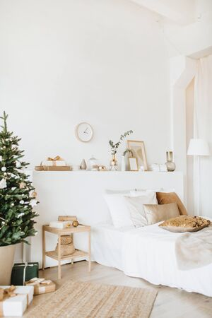 Modern interior design bedroom with Christmas / New Year decorations, toys, gifts, fir tree. Winter holidays composition.