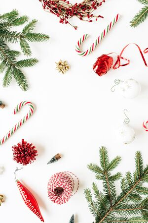 Christmas  New Year holiday composition. Mockup frame with blank copy space, fir needle branches, Christmas baubles, sweets, decorations on white background. Flat lay, top view festive concept. Stock Photo