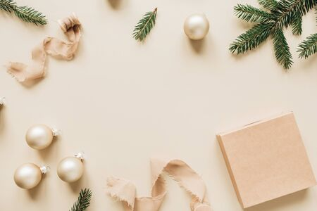 Christmas / New Year holiday composition. Mock up frame with blank copy space, fir needle branches, gift box, ribbons and Christmas baubles on beige background. Flat lay, top view festive concept. Reklamní fotografie