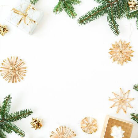 Christmas / New Year holiday composition. Frame with copy space of fir branches, gift boxes, straw decorations on white background. Flat lay, top view festive mockup.