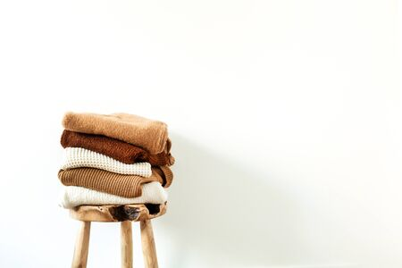Women fashion composition. Warm winter female woolen knitted sweaters, pullovers stack on wooden stool at white background. Modern clothes concept for magazine, blog, social media. Reklamní fotografie - 135492876