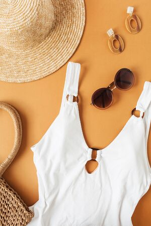 Travel fashion collage with female clothes and accessories on ginger background. Swimsuit, straw hat, rattan bag, sunglasses, earrings. Flat lay, top view fashion, beauty, travel blog.