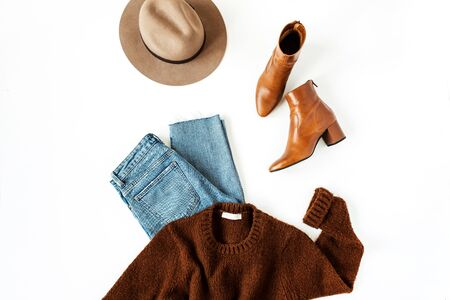 Flat lay fashion collage with women modern clothes and accessories on white background. Brown woolen pullover, shoes, hat, jeans. Lifestyle, beauty concept for blog, social media, magazine. Banque d'images - 135492886