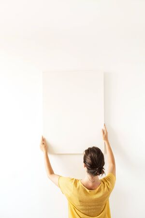 Young woman in yellow blouse hold blank canvas with empty mockup copy space. Minimal art concept.